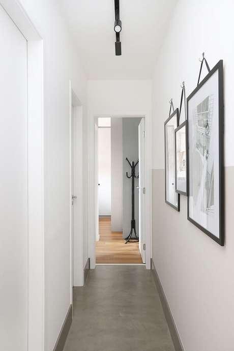 3. Piso de cimento queimado e iluminação com luminária para corredor pequeno do tipo trilho. Projeto por Inside Arquitetura e Design