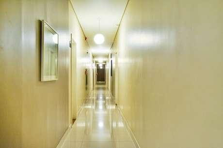 47. Projeto com piso de porcelanato e luminária pendente para corredor. Projeto por Bender Arquitetura