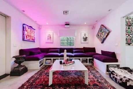 10. A luz embutida rosa traz uma atmosfera ousada combinada ao sofá roxo. Fonte: Pinterest