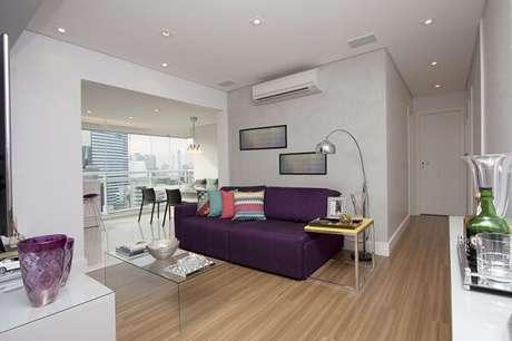 12. A mesa de centro transparente traz equilíbrio para a decoração da sala com sofá roxo. Projeto por Bianchi & Lima Arquitetura