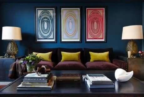 15. As almofadas amarelas sobra o sofá roxo trazem luz para a decoração. Fonte: Pinterest