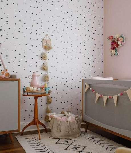 12. Mesa de canto para quarto de bebê decorado com papel de parede de bolinhas e berço cinza – Foto: MamãeAchei!
