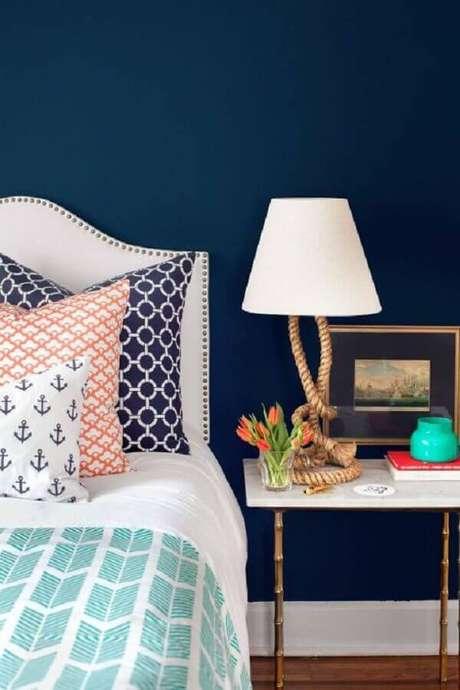 34. Abajur diferente para decoração de mesa de canto para quarto decorado com parede azul marinho – Foto:Better Homes and Gardens