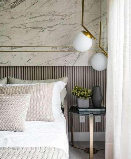 43. Mesa de canto redonda para quarto sofisticado decorado com luminária moderna e parede de mármore – Foto: Behance