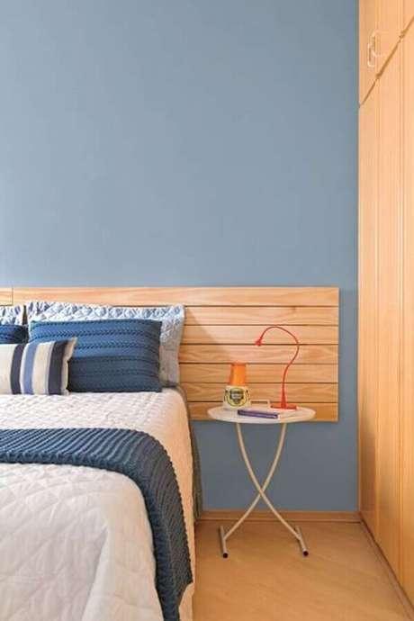 44. Mesa de canto pequena para quarto azul decorado com cabeceira de madeira – Foto: Pinterest