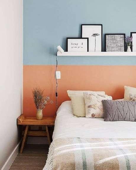 50. Mesa de canto de madeira para decoração de quarto simples com parede na cor coral e azul – Foto: A Casa Delas