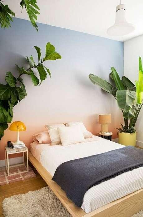 52. Mesa de canto para quarto de casal decorado com vaso de planta grande parede degrade – Foto: Histórias de Casa