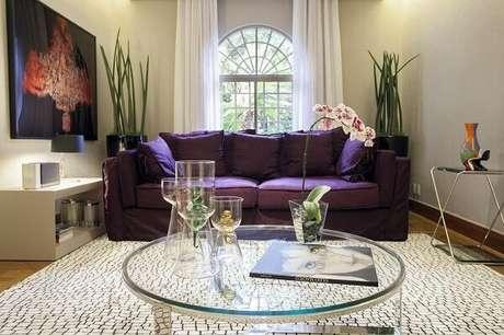 31. O sofá roxo contrasta com as cores claras das paredes e tapete da sala de estar. Fonte: Deborah Basso