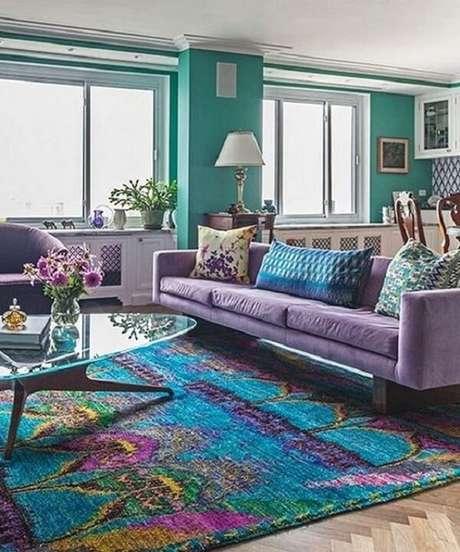 36. O sofá roxo de 3 lugares conversa diretamente com o tapete estampado. Fonte: Pinterest
