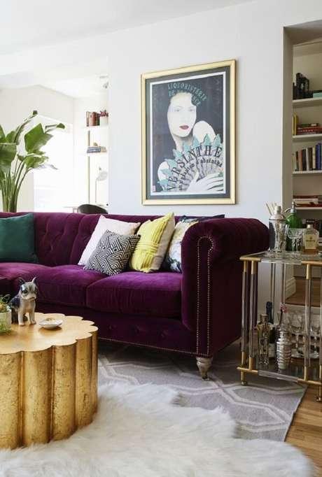 3. O sofá roxo escuro quebra a neutralidade da decoração desse ambiente. Fonte: Domino Magazine