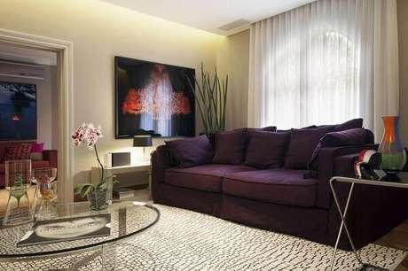 45. O sofá roxo traz um toque de cor para a decoração da sala de estar. Projeto por Deborah Basso