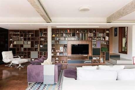 4. O tapete com estampa geométrica apresenta nuances em roxo conversando diretamente com o sofá roxo do local. Projeto por A.M Studio Arquitetura