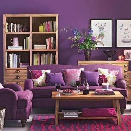 48. Os móveis em madeira trazem um contraste para a poltrona e sofá roxo. Fonte: Pinterest