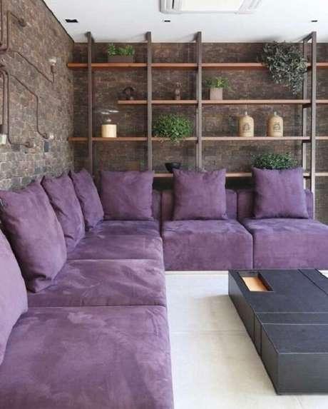 52. Sala contemporânea com sofá de canto roxo e parede de tijolinho aparente. Fonte: Pinterest
