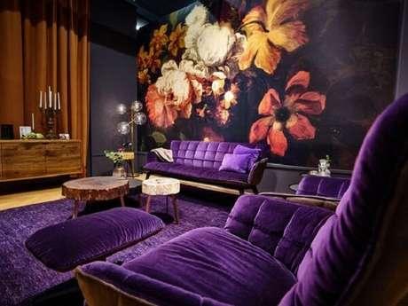 58. Sofá roxo e papel de parede floral decoram esse ambiente. Fonte: Pinterest