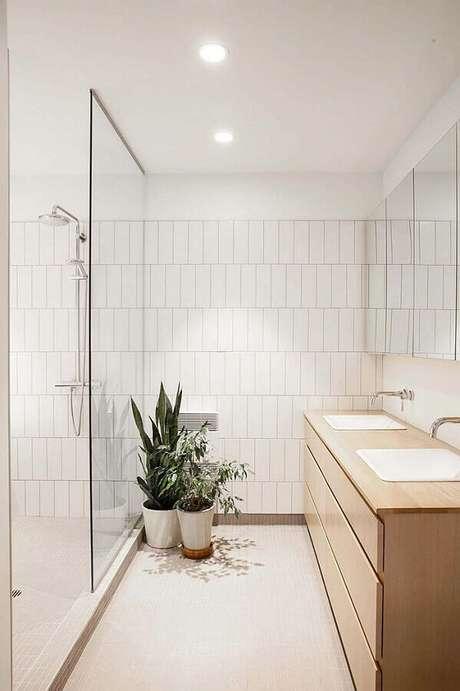 18. Decoração clean com gabinete de madeira clara e revestimento branco liso para banheiro – Foto: HomeDeco