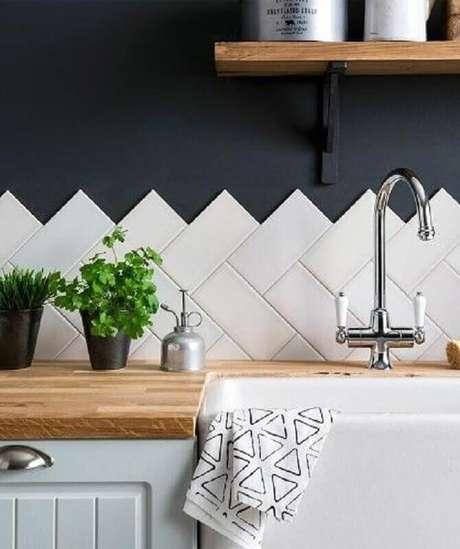 20. Revestimento cerâmico branco para decoração de cozinha com parede azul escura e bancada de madeira – Foto: Casa Montada