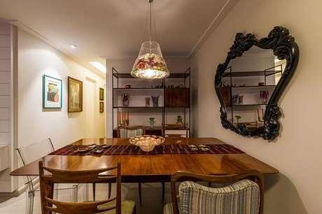 43. Espelho com moldura vintage decora a sala de jantar. Projeto por Enzo Sobocinski
