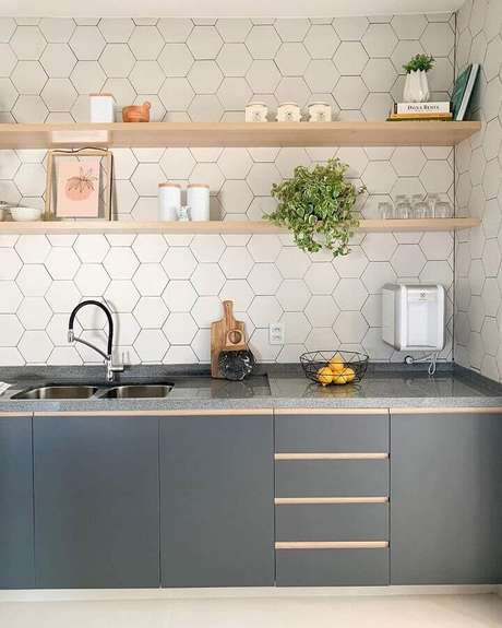 38. Revestimento hexagonal branco para decoração de cozinha planejada com prateleiras de madeira – Foto: Estúdio GT Arquitetura