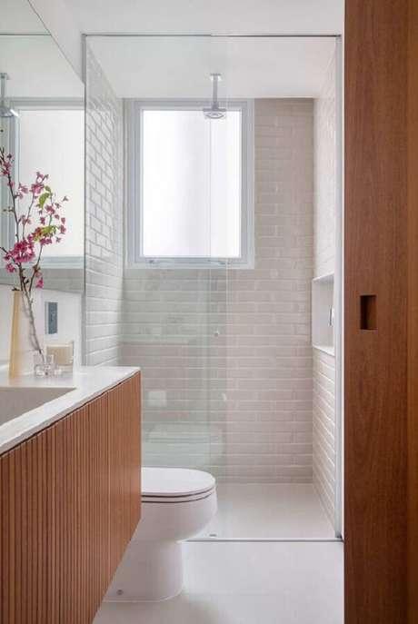 44. Revestimento branco para banheiro pequeno decorado com gabinete de madeira – Foto: Casa de Valentina