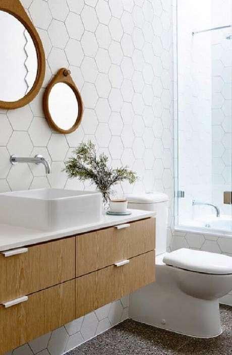 55. Decoração com revestimento hexagonal branco para banheiro com gabinete e espelhos de madeira – Foto: Apartment Therapy