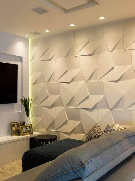 61. Decoração de sala de TV com revestimento 3D branco – Foto: Castelatto Pisos e Revestimentos