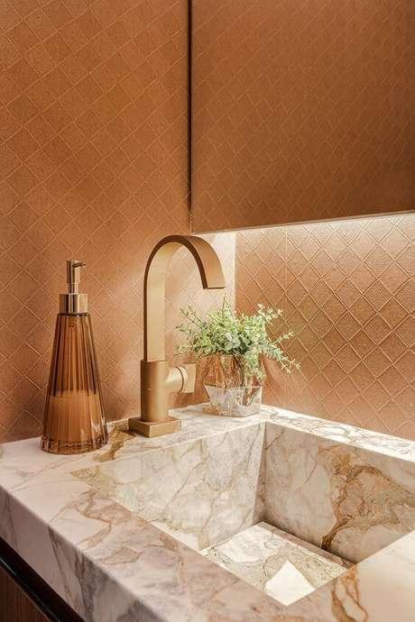 1. Banheiro luxuoso com cuba de mármore e detalhes em dourado – Via: ARD Studio