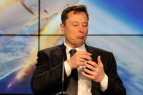 Elon Musk observa o smartphone durante conferência REUTERS/Steve Nesius/