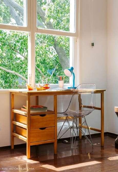 58. A escrivaninha de madeira maciça posicionada próxima a janela recebe muita luz natural. Fonte: Pinterest