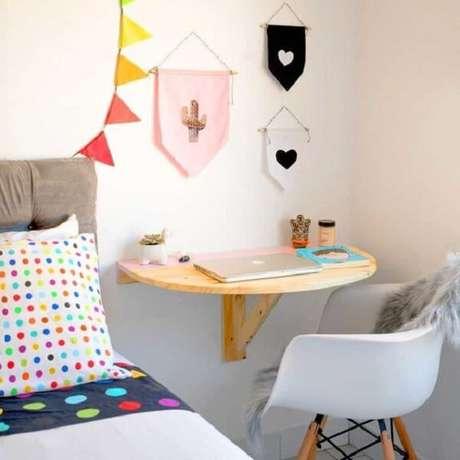 26. Escrivaninha de madeira rústica suspensa em formato meia lua otimiza o espaço do quarto. Projeto por DIYcore com Karla Amadori