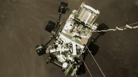 Robô Perseverance quando estava pousando em Marte, visto do foguete que auxiliou em sua descida