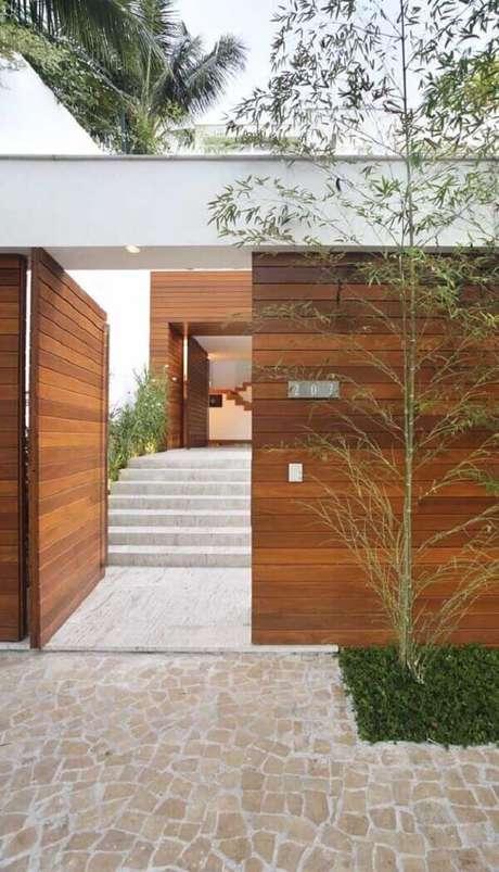50. Modelo de muro de frente de casa feito em madeira é durável e traz segurança ao imóvel. Fonte: Pinterest
