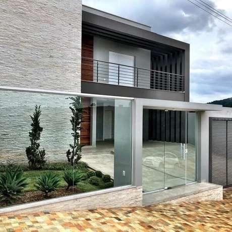 72. O modelo de frente de muro feito em vidro traz charme para a fachada da casa. Fonte: Ramsine Kézia Arquitetura