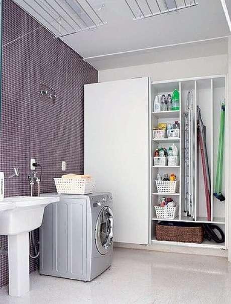 43. Armário planejado e revestimento para lavanderia com pastilha de vidro roxa. Fonte: Manual da Obra