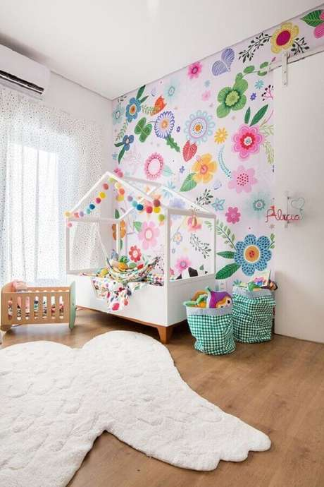 55. Decoração de quarto para criança menina com cama casinha e papel de parede floral colorido – Foto: MOOUI