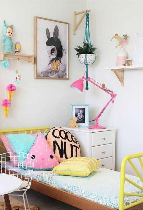 21. Decoração simples de quarto para criança menina com almofadas divertidas e luminária cor de rosa – Foto: Pinterest