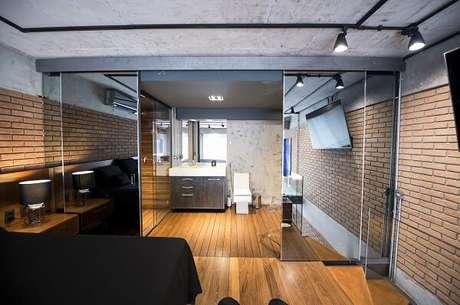 8. Parede de tijolinho aparente e porta para quarto de correr espelhada marcam a decoração do espaço. Fonte: Carla Cuono Arquitetura e Interiores