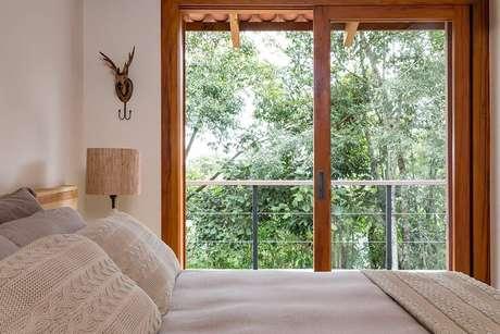 47. A porta de correr para quarto de vidro com acabamento em madeira permite a visão da paisagem do entorno do imóvel. Fonte: RAP Arquiteutra e Interiores