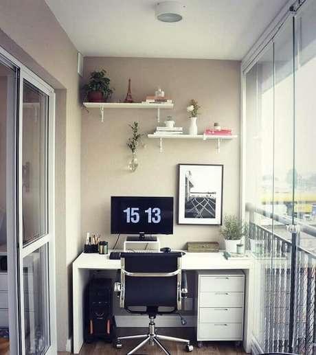 24. Escrivaninha branca e cadeira pé cromado para home office na varanda. Fonte: Carreira Fácil
