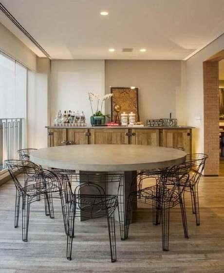 46. A cadeira cromada preta decora a varanda com buffet de madeira. Fonte: Triplex Arquitetura