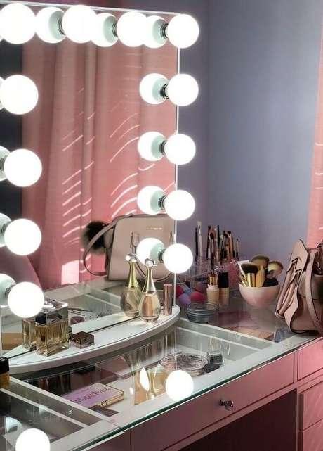 3. Penteadeira rosa camarim com tampo de vidro facilita a visualização dos itens no móvel. Fonte: Pinterest