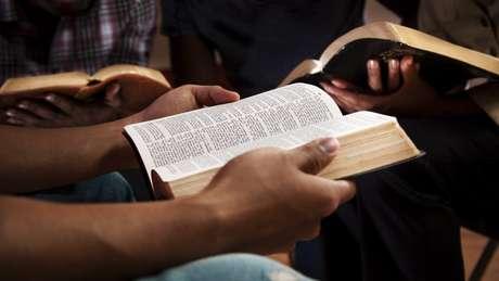Close nas maos de pessoas segurando biblias em uma roda de conversa