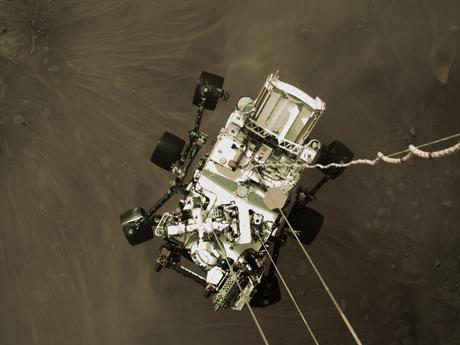 As primeiras fotos enviadas de volta foram feitas durante a descida do robô. Aqui, o Perseverance está sendo baixado em três cordas de náilon e um 'cordão umbilical'. Quando as rodas do veículo espacial tocaram o solo, as amarras foram cortadas