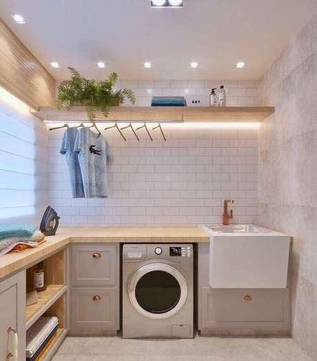 40. Decoração em cores neutras com prateleira de madeira para lavanderia planejada em L. Foto: Pinterest