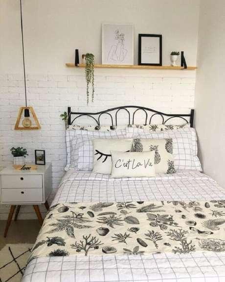 22. Decoração com mesa de cabeceira retrô branca e parede de tijolinho aparente. Fonte: Pinterest