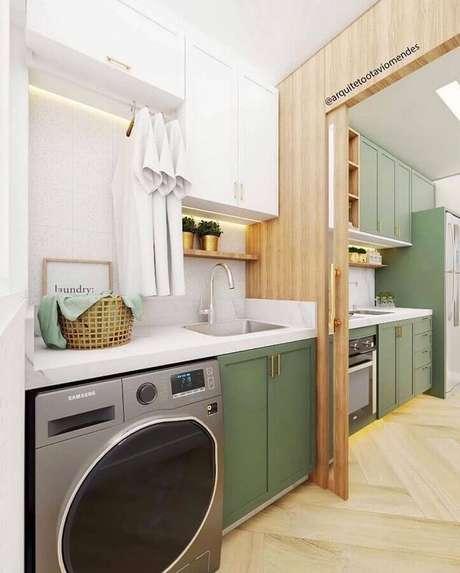 44. Decoração com prateleira para lavanderia planejada com armários brancos e verdes e divisória de madeira. Foto: Arquiteto Otávio Mendes