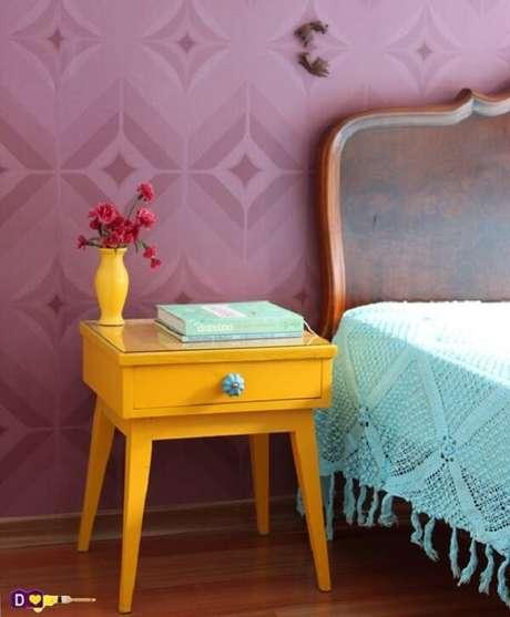 50. Quarto colorido com mesa de cabeceira retrô amarela, papel de parede roxo e colcha azul. Fonte: Pinterest