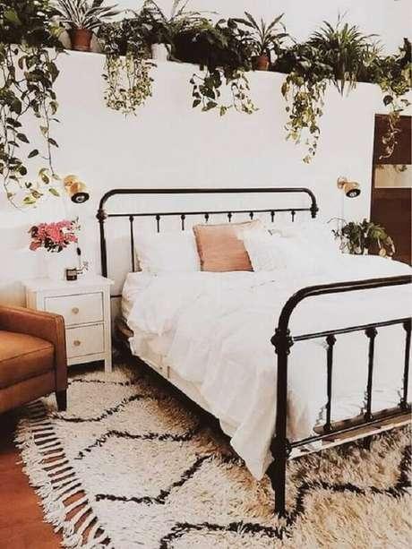 56. Quarto romântico decorado com vários vasos de plantas, cama de ferro e mesa de cabeceira retrô branca com gavetas. Fonte: A Casa Delas