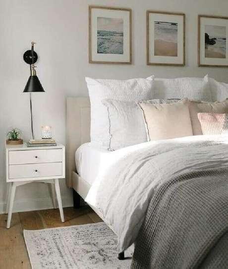 33. Mesa de cabeceira retrô branca decora o quarto de casal com arandela preta moderna. Foto: Isabella Simth