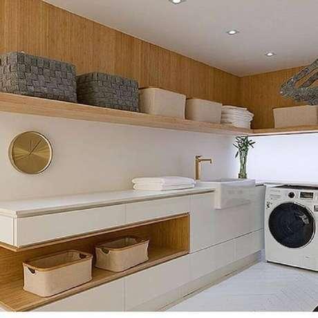 41. Decoração em cores neutras com prateleira de parede para lavanderia planejada com detalhes em madeira. Foto: Manual da Obra